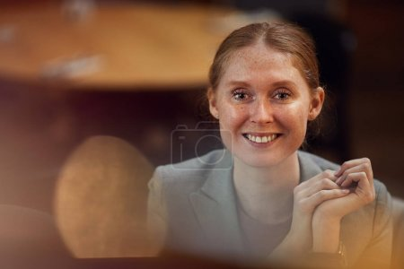 Photo for Portrait of successful red haired businesswoman smiling at camera while sitting at office - Royalty Free Image