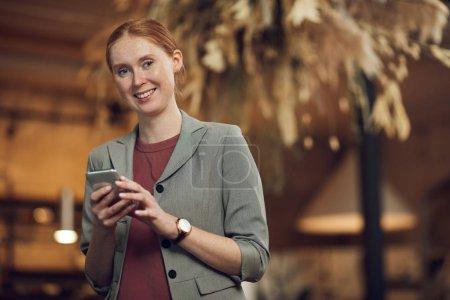 Photo pour Portrait de jeune femme d'affaires rousse debout et souriant à la caméra tout en utilisant le téléphone portable dans le café - image libre de droit