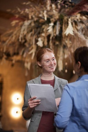 Photo for Young businesswoman smiling and discussing to colleague business documents while standing in the restaurant - Royalty Free Image