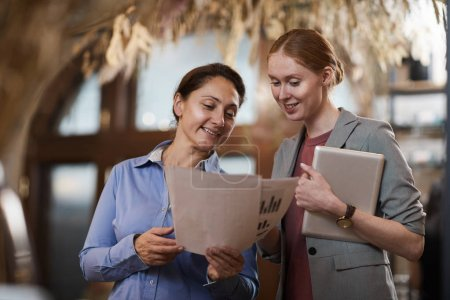 Photo for Two businesswomen standing and smiling reading financial report and satisfied with results - Royalty Free Image