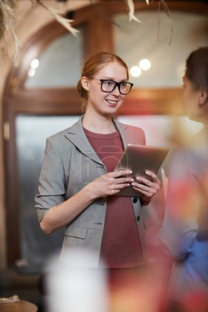 Photo for Young confident businesswoman in eyeglasses standing and holding tablet pc while talking to partner - Royalty Free Image