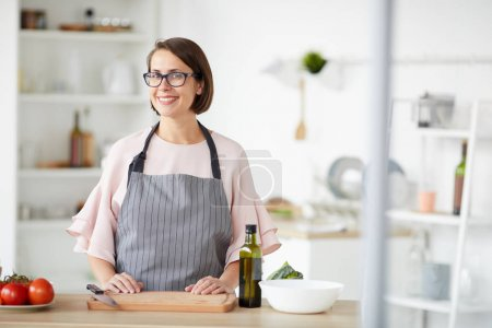 Photo for Portrait of young woman in eyeglasses and in apron smiling at camera while standing and cutting vegetables in the kitchen at home - Royalty Free Image