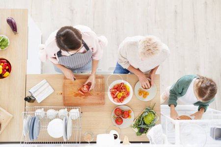 Photo for Family of three standing at the kitchen table and preparing vegetables for dinner together in the kitchen at home - Royalty Free Image