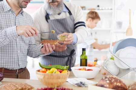 Photo for Close-up of young man standing and tasting sauce giving by the mature man while they preparing food in the kitchen - Royalty Free Image