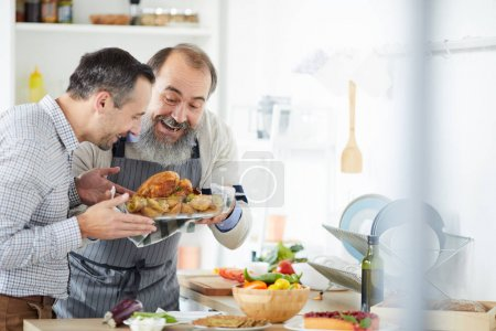 Photo for Senior man with beard and young man holding dish of roast turkey prepared for dinner at home - Royalty Free Image