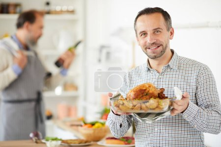 Photo for Young man holding dish of roast turkey prepared for holiday with senior man cooking in the background in domestic kitchen - Royalty Free Image