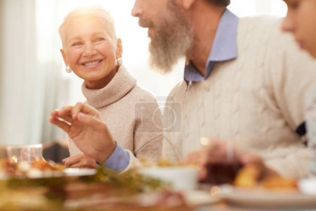 Photo for Mature woman with short blond hair smiling to the senior man while talking at the table during dinner - Royalty Free Image