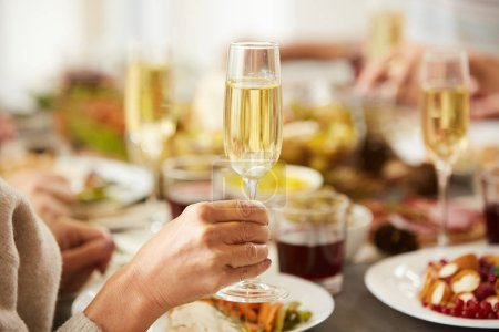Photo pour Close-up of female hand holding glass with champagne while have dinner at the table - image libre de droit