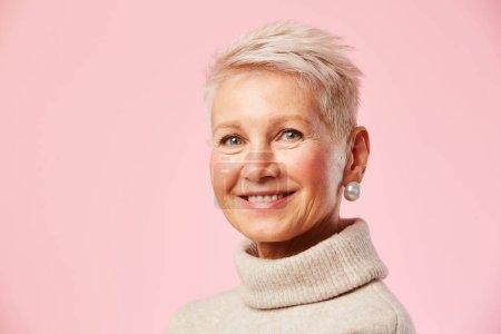 Photo pour Portrait d'une femme mature heureuse souriant à la caméra sur fond rose - image libre de droit