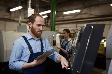 Photo for Serious bearded engineer controlling the work of machine with tablet pc with colleague working in the background - Royalty Free Image