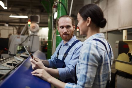 Photo for Two engineers in overalls using digital tablet and talking to each other during work in the plant - Royalty Free Image