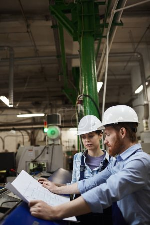 Photo for Two engineers in special work wear and in hardhats looking at blueprint and discussing together in the factory - Royalty Free Image
