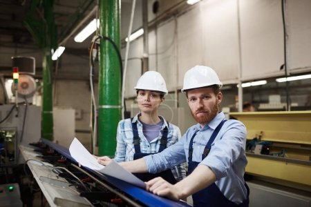 Photo for Portrait of two engineers in overalls and hardhats looking at camera while working with blueprint in the factory - Royalty Free Image
