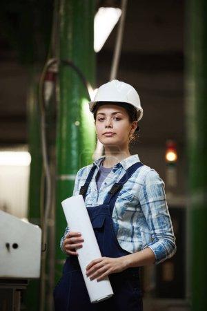 Photo pour Portrait d'une ingénieure confiante en salopette et en casque de travail regardant la caméra debout dans l'usine - image libre de droit