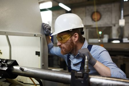 Serious manual worker in protective workwear and protective glasses working on lathe in the plant