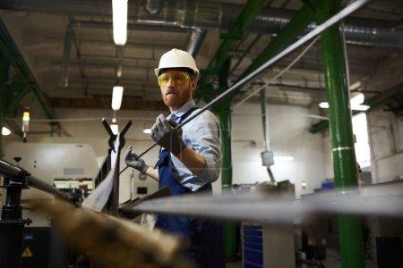 Photo pour Travailleur manuel en tenue de travail et lunettes de protection portant des gants tenant un tuyau de fer pendant qu'il travaille à l'usine - image libre de droit