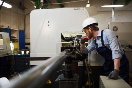 Photo pour Jeune opérateur de lunettes de protection et de vêtements de travail debout et travaillant sur du tour en usine - image libre de droit