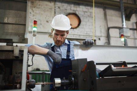 Photo pour Ingénieur grièvement barbu en casque de travail se concentrant sur le travail de surveillance du travail de machine dans l'usine - image libre de droit