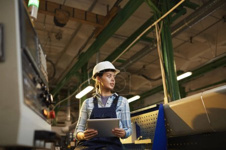 Photo pour Technicienne en casque de travail contrôlant le travail de la machine avec comprimé numérique dans l'usine - image libre de droit
