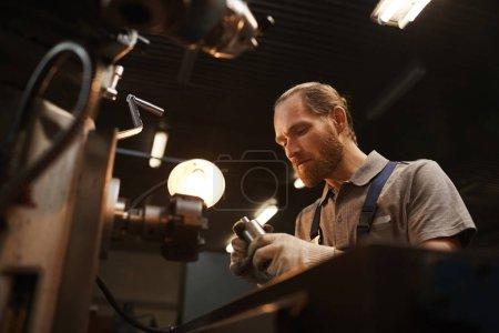 Photo pour Mécanicien grièvement barbu travaillant sur une machine en usine - image libre de droit