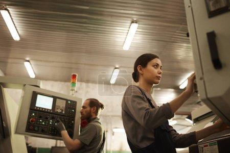 Photo pour Une femme sérieuse au travail porte debout et contrôle le travail de la machine avec un collègue à l'arrière-plan - image libre de droit