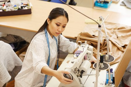 Photo for Asian young seamstress working with sewing machine sewing clothes in workshop - Royalty Free Image
