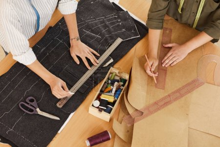 Photo for Close-up of two tailors drawing patterns and working with fabrics in team at the table in workshop - Royalty Free Image