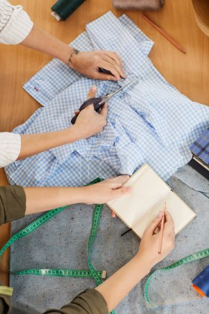Photo for Close-up of tailor cutting fabric with scissors and student learning to sew making notes in notepad during their sewing lesson - Royalty Free Image