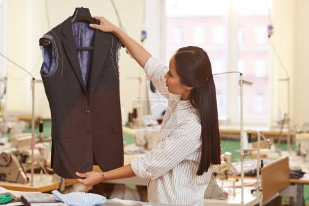 Photo for Asian young dressmaker holding unfinished suit in hands and examining it while working in workshop - Royalty Free Image