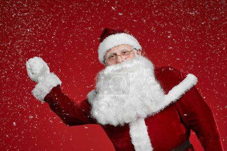 Photo for Portrait of Santa Claus in red costume playing snowballs on red background - Royalty Free Image