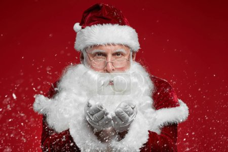 Photo for Portrait of Santa Claus with white beard blowing snowflakes in hands and looking at camera over red background - Royalty Free Image