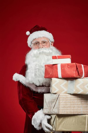 Photo for Portrait of Santa Claus in red costume holding Christmas presents in hands and looking at camera on red background - Royalty Free Image