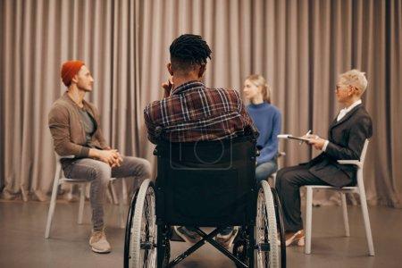 Photo pour Vue arrière du jeune Africain assis en fauteuil roulant et écoutant les gens pendant la réunion - image libre de droit