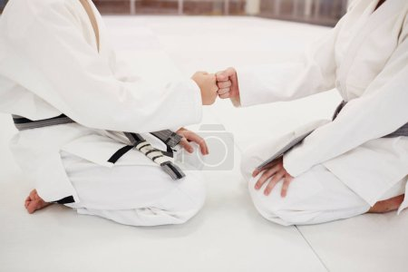 Close-up of little fighters in kimono clenched their fists and greeting each other before fight