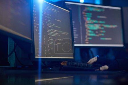 Photo pour Image de moniteurs d'ordinateur avec un logiciel debout sur la table dans le bureau sombre - image libre de droit