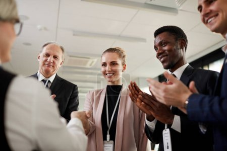 Photo for Multiethnic group of business people standing and applauding to the leader after conference - Royalty Free Image