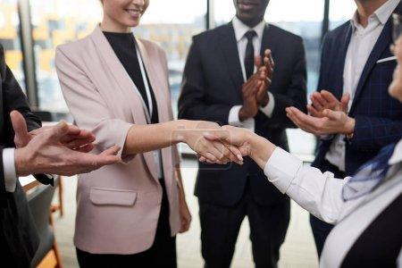 Photo pour Groupe de gens d'affaires se tenant debout et serrant la main à leur collègue et le félicitant - image libre de droit