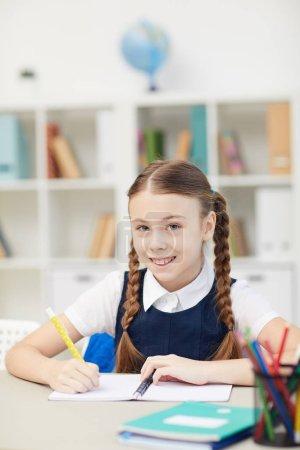 Photo pour Portrait d'écolière mignonne souriant à la caméra alors qu'elle était assise au bureau et écrivait dans un cahier - image libre de droit