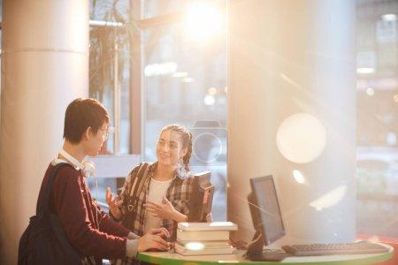Photo pour Deux élèves utilisent un ordinateur portable et se parlent pendant qu'ils passent du temps à la bibliothèque - image libre de droit