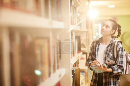 Photo for Young woman holding books and making a list of books for studying before the exam while standing near the bookcase at the library - Royalty Free Image