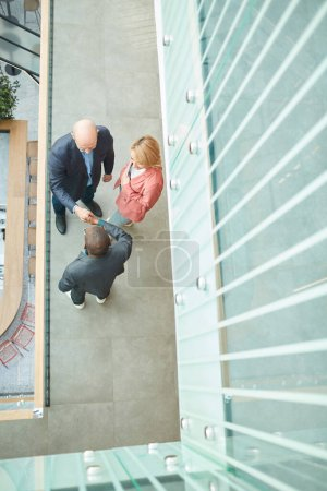 High angle view of business people shaking hands t...