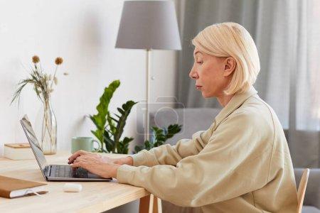 Foto de Mujer madura seria que se concentra en su trabajo en línea en el ordenador portátil en la mesa en casa - Imagen libre de derechos