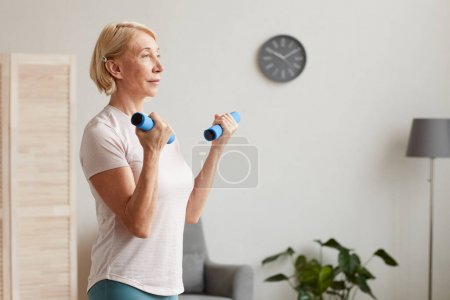 Photo for Senior woman with blond short hair holding dumbbells in her hands and exercising while standing in the room - Royalty Free Image