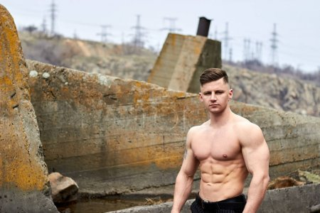 Photo for Attractive young guy demonstrates muscular torso outdoors. Beautiful physique. Fitness and lifestyle concept. Pronounced muscles of the press. Athletic physique. - Royalty Free Image