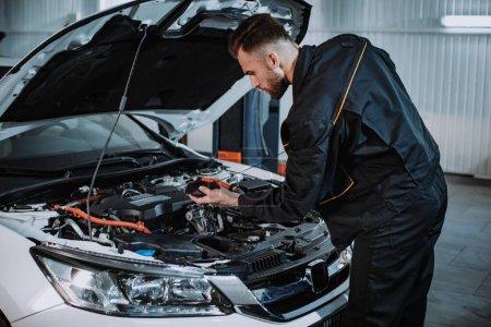 Photo pour Bon mécanicien dans un service moderne auto vérifier soigneusement le niveau d'huile de la voiture . - image libre de droit