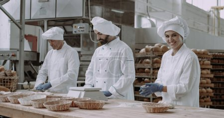 Photo pour Femme boulangère très charismatique avec un grand sourire et ses collègues formant la pâte à cuire le pain, processus de fabrication du pain, industrie alimentaire . - image libre de droit