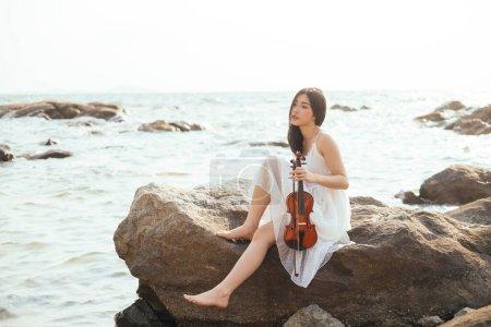 Photo pour Fille assise sur le rocher de mer avec violon . - image libre de droit