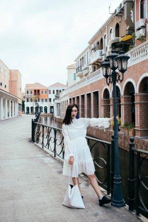 Photo pour Belle femme vêtue d'une robe blanche agrippant un lampadaire. - image libre de droit