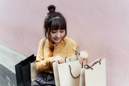 Photo for Cute girl wearing yellow sweater opening a paper bag. - Royalty Free Image