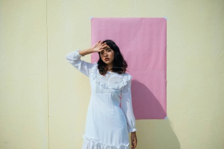 A girl in white dress standing infront of the yellow wall with pink wallpaper under the strong sunshine.